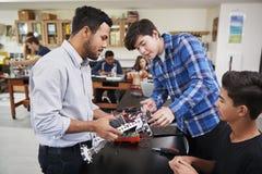 Lärare With Male Pupils som bygger det Robotic medlet i vetenskapskurs royaltyfria foton