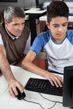 Lärare With Male Student som använder datoren på skrivbordet Arkivfoto