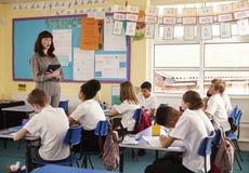 Lärare med datoren som är främst av grundskola för barn mellan 5 och 11 årgrupp Royaltyfria Bilder