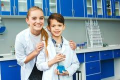 Lärare med det lilla barnet i den bästa studenten för skolalaboratorium royaltyfri fotografi