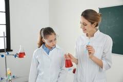 Lärare med eleven som gör experiment i grupp arkivfoton