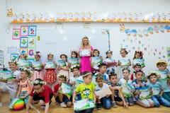 Lärare med en grupp av första väghyvelbarn på den sista dagen av skolan arkivbild