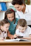 Lärare med henne elever undersöker något fotografering för bildbyråer