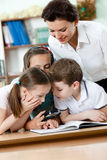 Lärare med henne elever undersöker något Royaltyfri Foto