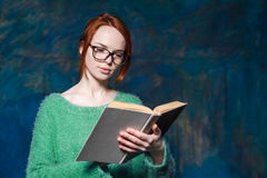 Lärare med rött hår i exponeringsglas som läser den gamla boken Arkivbilder