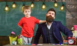 Lärare med skägget, fader och liten son som har gyckel i klassrumet, svart tavla på bakgrund Gladlynt barn och lärare arkivbilder