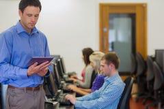 Lärare med studenter som använder datorer i datasal Arkivbild
