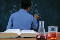 Lärare med vetenskaplig sakkunskap Boken är öppen och dryckeskärlen på royaltyfri bild