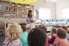 Lärare At Montessori School som läser till barn på berättelsen Tid Royaltyfri Fotografi