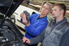 Lärare och deltagare i utbildning för auto mekaniker som utför prov på mekanikerskolan royaltyfria foton