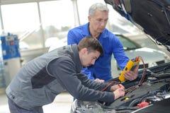 Lärare och deltagare i utbildning för auto mekaniker som utför prov på mekanikerskolan royaltyfri bild