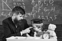Lärare och elev i akademikermössan, svart tavla på bakgrund Lura gladlynt distrahera, medan studera, uppmärksamhetunderskottet royaltyfri fotografi