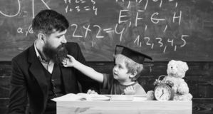 Lärare och elev i akademikermössan, svart tavla på bakgrund Lura gladlynt distrahera, medan studera, uppmärksamhetunderskottet arkivbild
