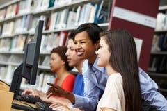 lärare och elever som arbetar på datorer royaltyfri fotografi