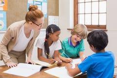 Lärare och elever som tillsammans arbetar på skrivbordet Royaltyfria Bilder