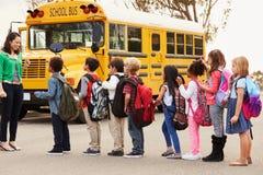 Lärare och en grupp av grundskolaungar på en hållplats arkivbilder