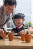 Lärare och skolflicka som planterar växter in i blomkrukor Arkivfoto