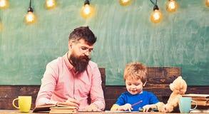 Lärare och små ungehandstilbokstäver i förskriftsbok Gullig pojke som drar en bild med färgrika blyertspennor Konstkurs på arkivfoto