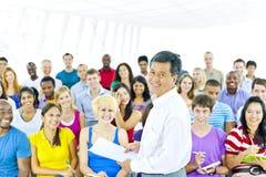 Lärare och stor grupp av studenten i föreläsningsrum Arkivbilder