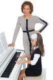 Lärare och student på pianot Fotografering för Bildbyråer