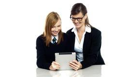 Lärare och student som är upptagna i minnestavlaapparat Arkivfoton