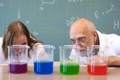 Lärare och studenter analyserar kemikalieer Arkivfoto
