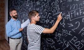 Lärare- och studenthandstil på den stora svart tavla med matematiskt Arkivfoto