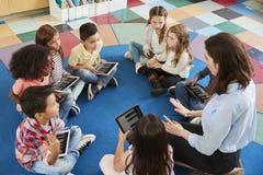 Lärare och ungar i en grundskolakurs med minnestavlor arkivbild