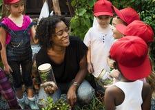 Lärare- och ungeskola som lär att arbeta i trädgården för ekologi Royaltyfri Bild
