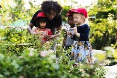 Lärare- och ungeskola som lär att arbeta i trädgården för ekologi Arkivfoto