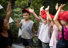 Lärare- och ungeskola som lär att arbeta i trädgården för ekologi Arkivfoton