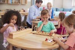 Lärare And Pupils Working på tabeller i den Montessori skolan royaltyfria foton