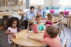 Lärare And Pupils Working på tabeller i den Montessori skolan arkivfoton