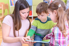 Lärare Showing en bok till barn på Nurceryen Arkivbilder