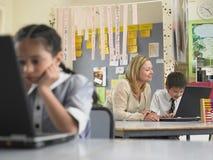 Lärare Sitting With Boy som använder bärbara datorn i grupp arkivfoto
