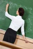 Lärare skriver med krita på blackboarden royaltyfria bilder