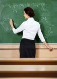 Lärare skriver på blackboarden royaltyfri fotografi