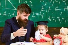 Lärare som förklarar nytt material till den lilla eleven Gullig unge i akademikermössan som spelar med papper Stilig grabb och gu Royaltyfri Foto