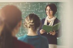 Lärare som ger kurs till studenter i klassrum arkivbilder