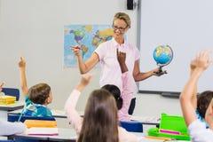 Lärare som har kurs med ett jordklot royaltyfria foton