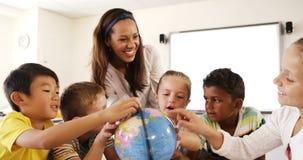 Lärare som hjälper skolaungar i läs- jordklot i klassrum arkivfilmer