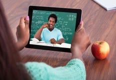 Lärare som hjälper studenten till och med videoconferencing Arkivbild