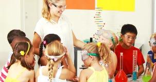 Lärare som hjälper ungar i laboratorium stock video