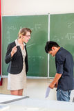 Lärare som kritiserar en elev i skolagrupp Royaltyfria Bilder