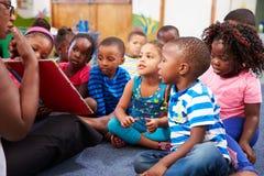 Lärare som läser en bok med en grupp av förskole- barn Arkivbilder