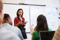 Lärare som lyssnar till studenter på en vuxenutbildninggrupp Royaltyfri Bild
