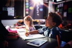 Lärare som påverkar varandra med skolpojken i klassrum arkivbilder