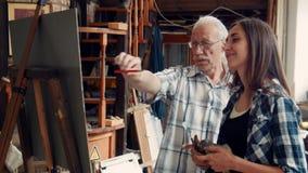 Lärare som undervisar en ung flicka att måla en bild i oljor arkivfilmer