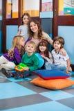 Lärare And Students Sitting på golv i klassrum royaltyfri foto