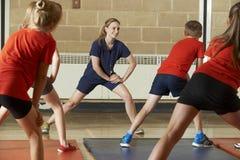 Lärare Taking Exercise Class i skolaidrottshall arkivfoto